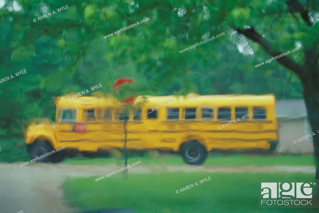 Stock Photo: Schoolbus at neighborhood corner, seen through rainy windshield.