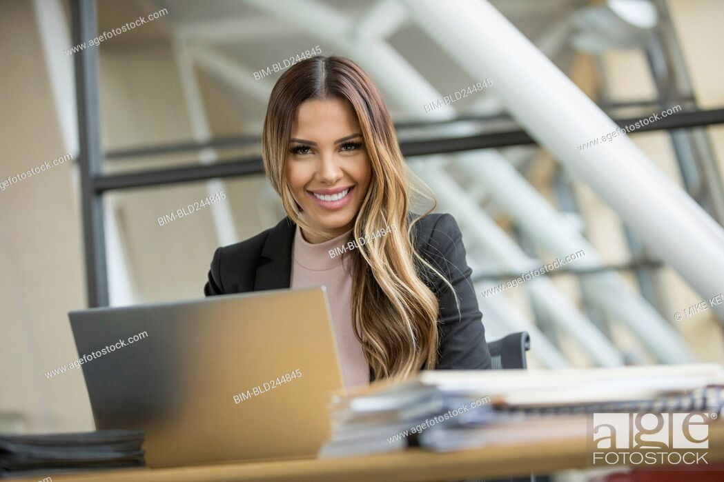 Stock Photo: Smiling Mixed Race businesswoman using laptop.