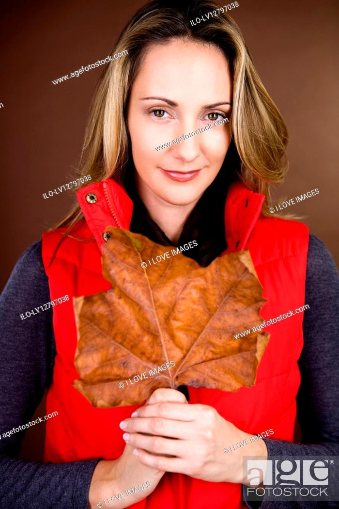 Stock Photo: A mid adult woman holding a dried leaf.