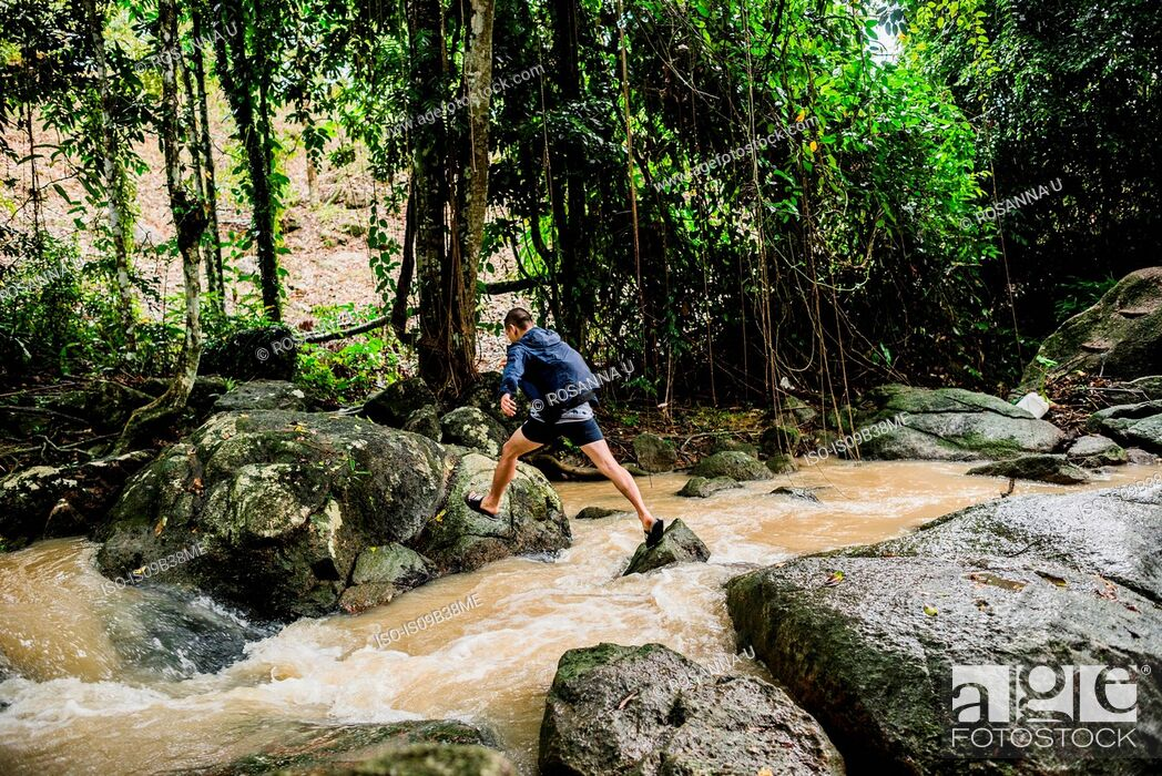 Imagen: Young man crossing stream, Secret Buddha Garden, Koh Samui, Thailand.