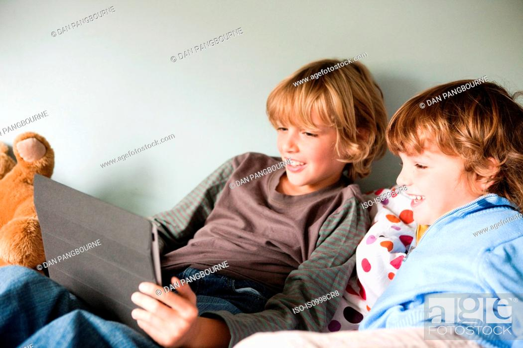 Stock Photo: Two young boys on a bed, using a digital tablet.