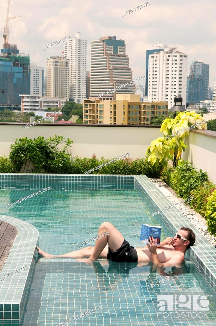 Stock Photo: Life at the top, relaxing with a book in a rooftop pool in Bangkok, Thailand.