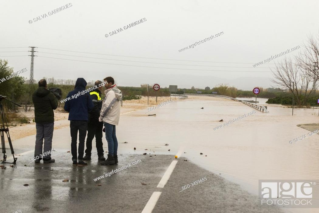 Stock Photo: Alberic, Valencia, Spain, January 21, 2020. Police interviewed by television when controlling the access of vehicles on the road flooded by the overflow of the.
