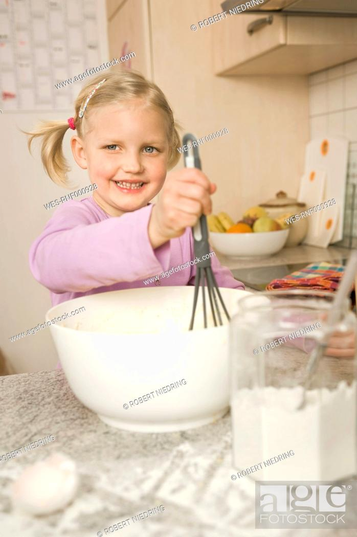 Stock Photo: Girl mixing batter in bowl, smiling.