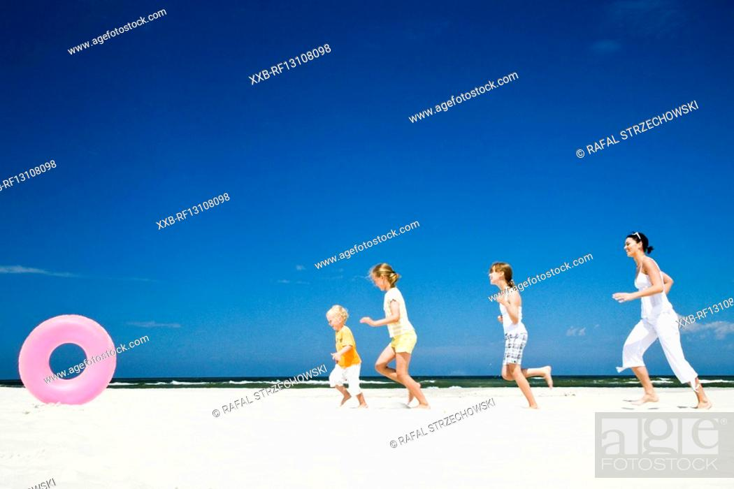 Stock Photo: kids running after ball on beach.