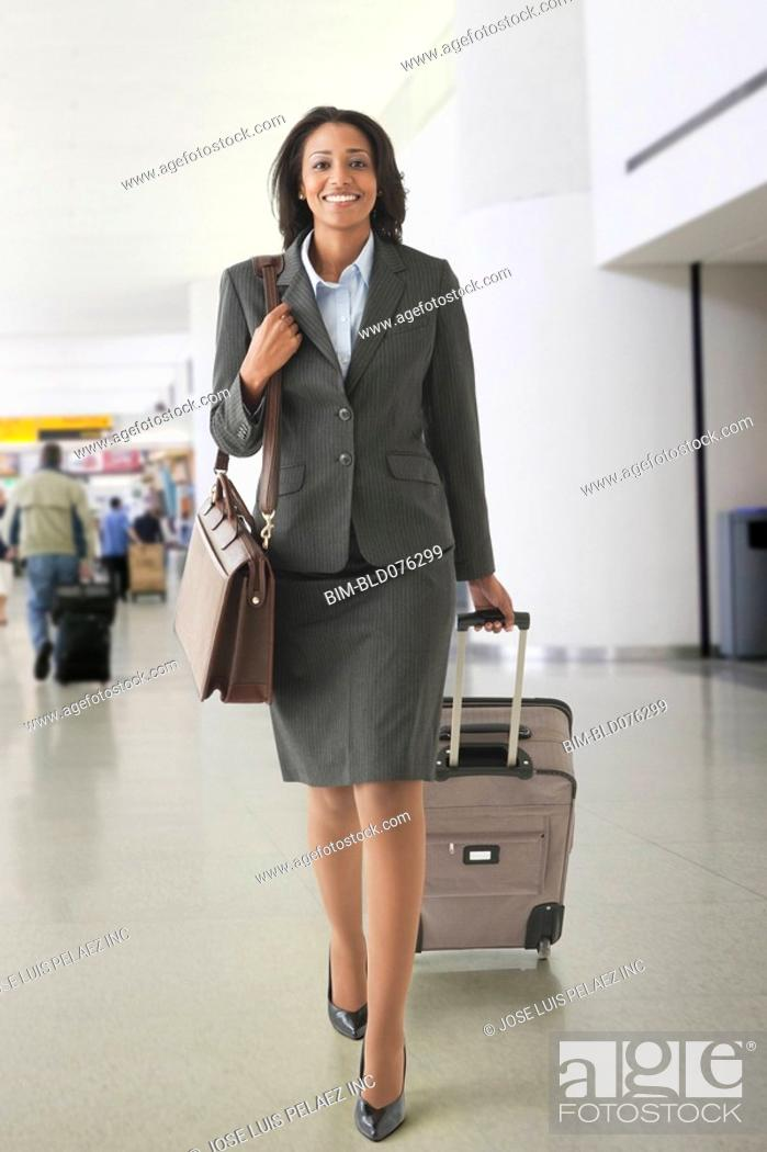 Stock Photo: African businesswoman pulling suitcase in airport.