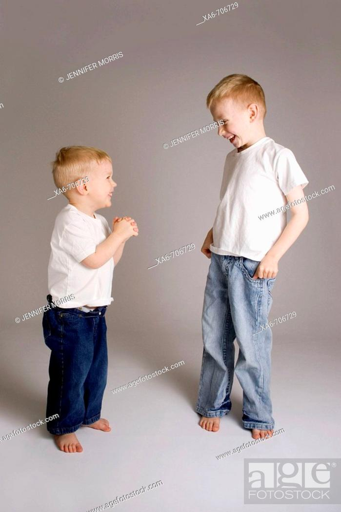 Stock Photo: Two blond haired brothers, 6 and 3 years old, wearing white t-shirts and blue jeans, look at each other and laugh, sharing a joke.