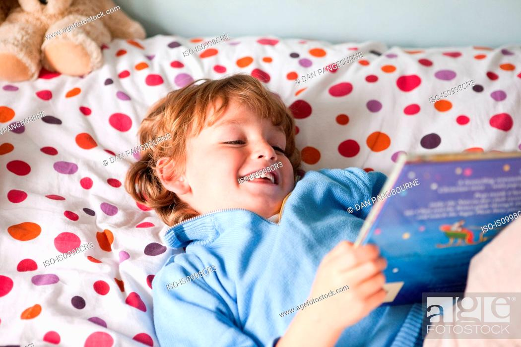 Stock Photo: Young boy reading a book on his bed.