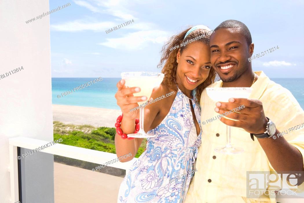 Stock Photo: Couple having drinks on balcony.