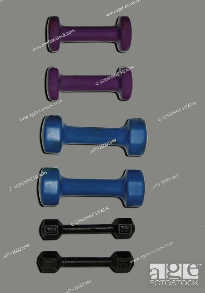 Stock Photo: Three sets of free weights on plain background.
