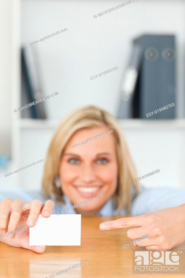 Stock Photo: Businesswoman pointing at a card crouching behind her desk.