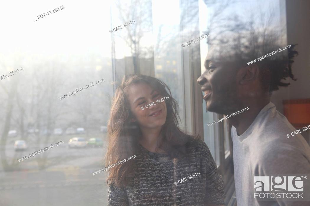 Stock Photo: A boyfriend and girlfriend laughing together, viewed through window.