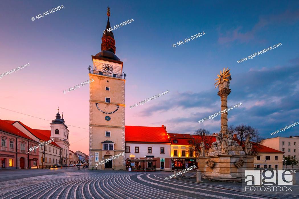 Stock Photo: Trnava, Slovakia - April 9, 2019: City tower and Holy Trinity Statue in the main square of Trnava, Slovakia.