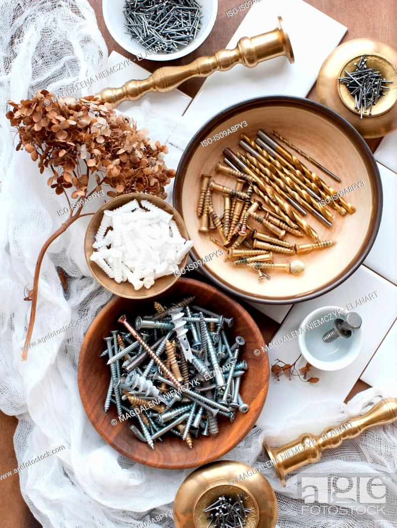 Stock Photo: Still life of screws, nails and brass candlesticks.