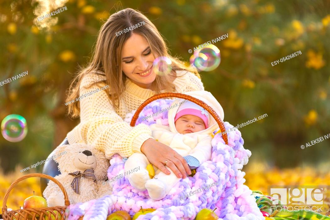 Stock Photo: Mom happily looks at the two-month-old baby sleeping in a basket, flying soap bubbles.