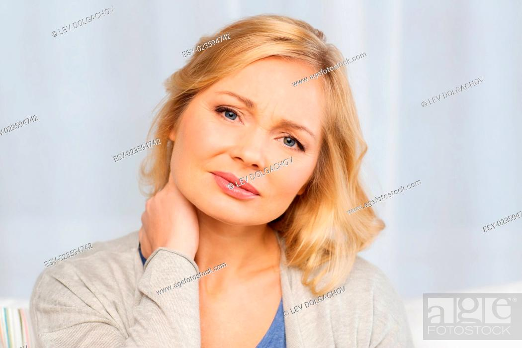 Stock Photo: people, healthcare and problem concept - unhappy woman suffering from neck pain at home.