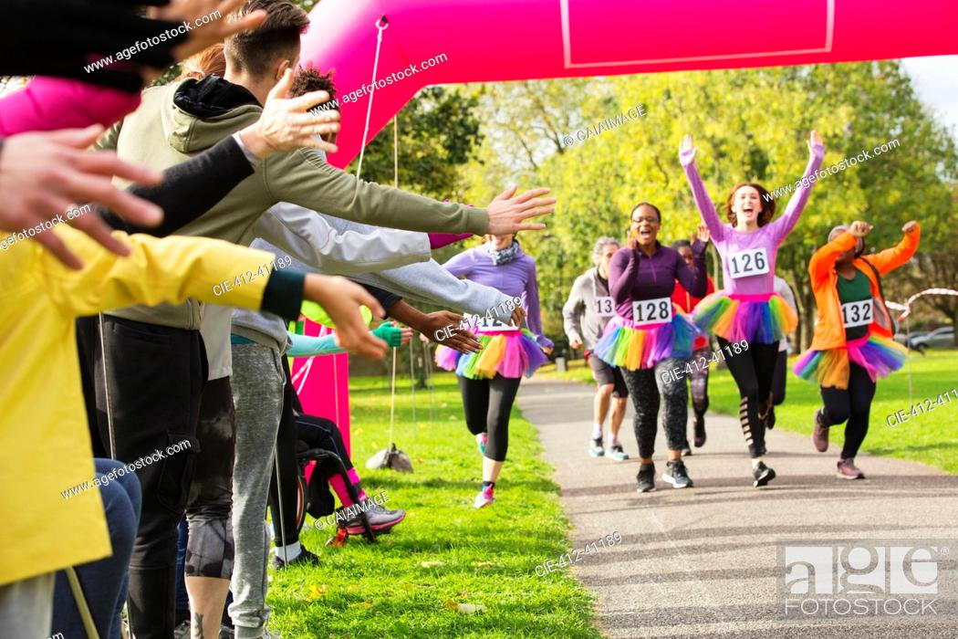 Photo de stock: Enthusiastic female runners in tutus nearing finish line at charity run in park.
