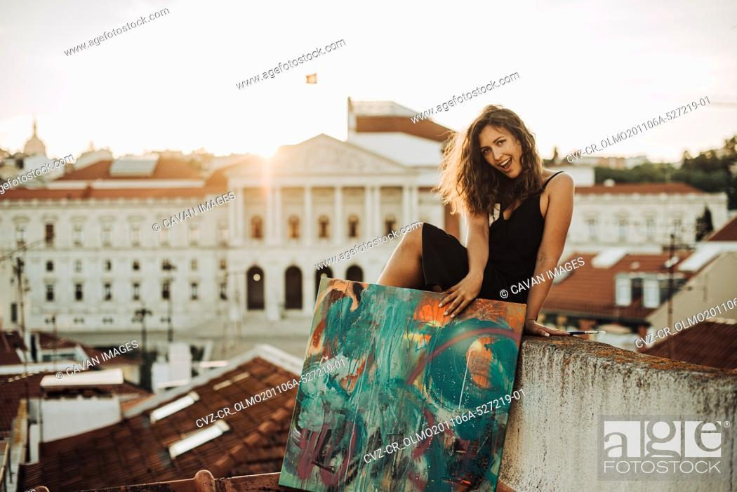Stock Photo: Happy smiling woman sitting on the roof holding abstract art painting.