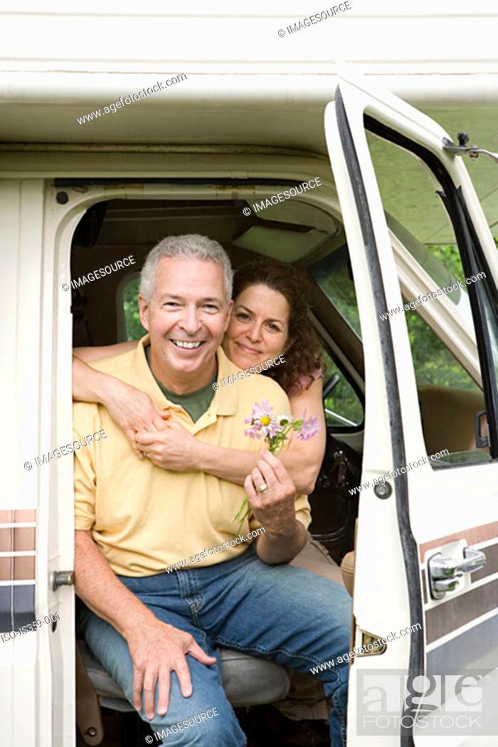 Stock Photo: Mature couple hugging in caravan.
