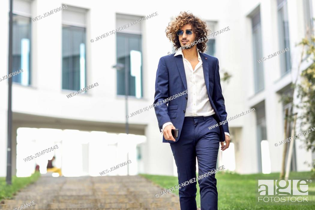 Photo de stock: Portrait of young fashionable businessman with curly hair wearing blue suit and sunglasses.