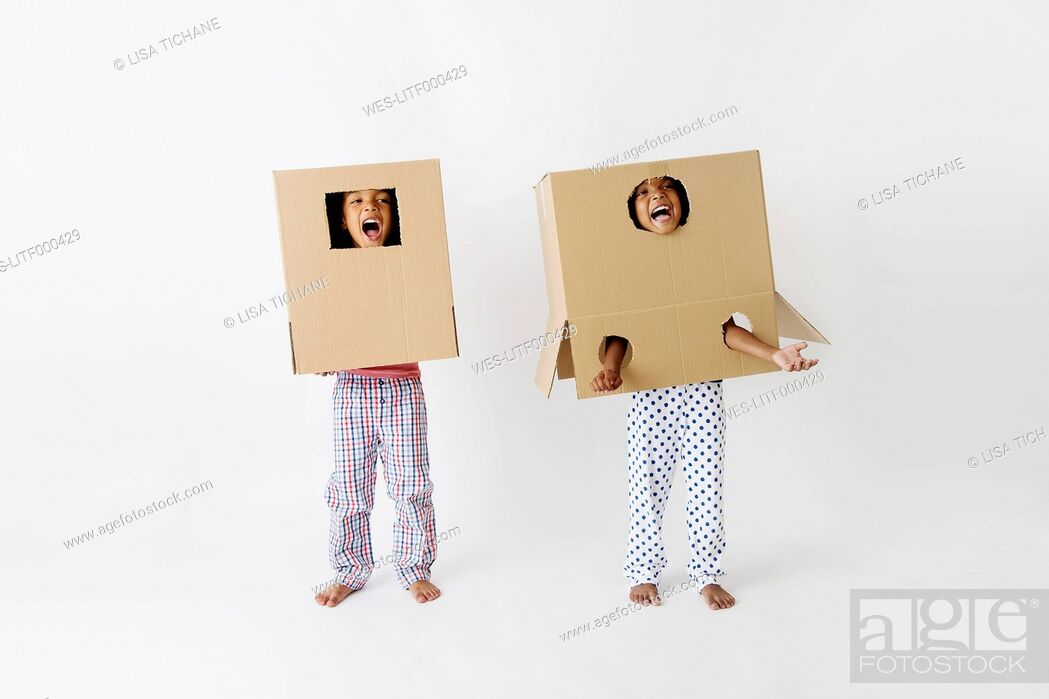 Stock Photo: Two little children with cardboard boxes on their heads.