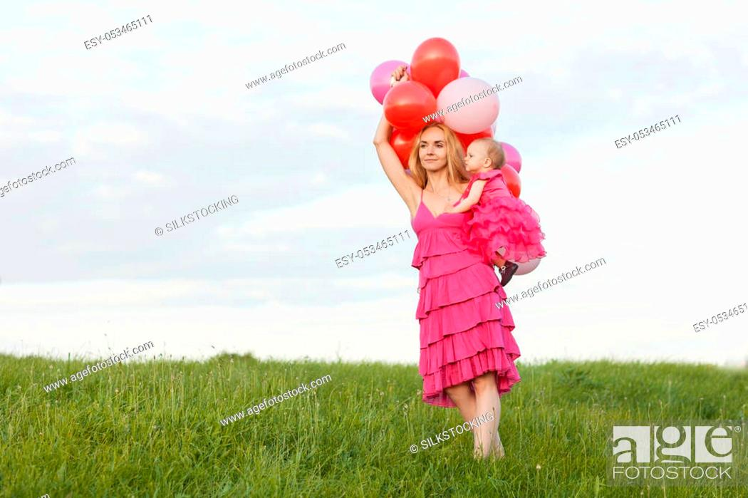 Stock Photo: Mom holds a daughter and balloons in her hands. Mom is looking ahead.
