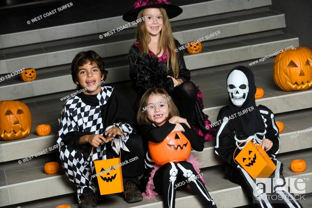 Stock Photo: Portrait of boys and girls 7-9 wearing Halloween costumes on steps.