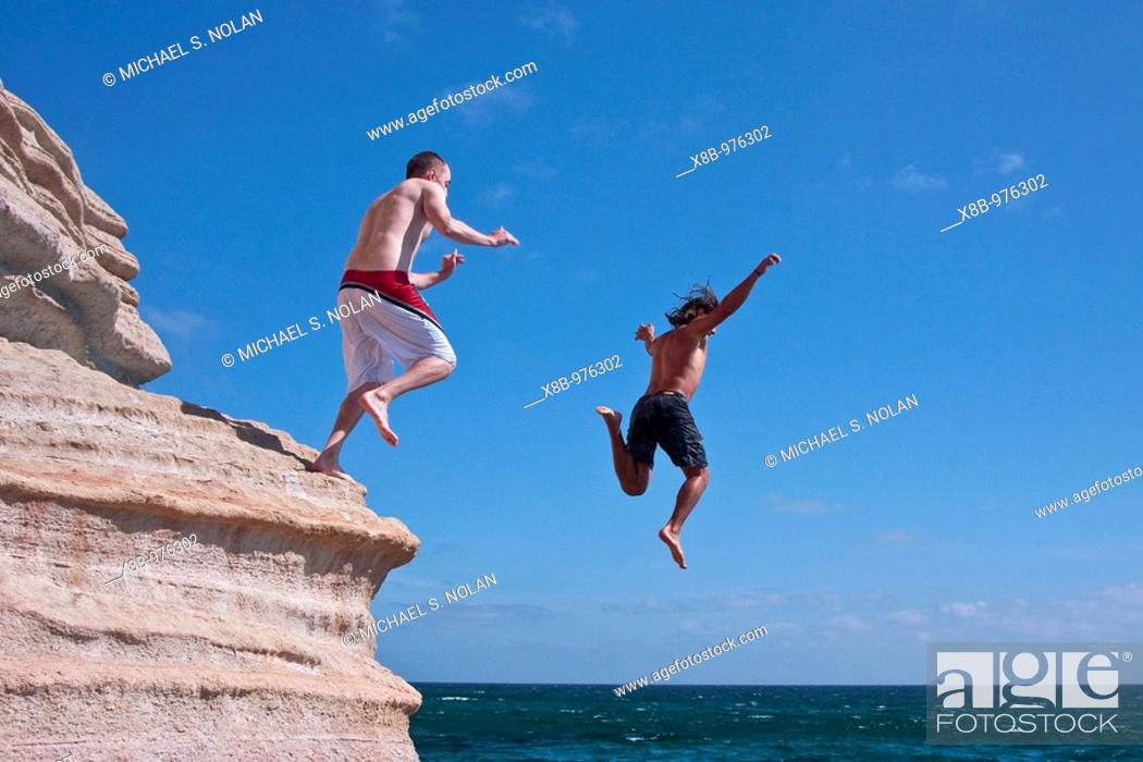 Stock Photo: The Lindblad expedition ship National Geographic Sea Lion staff diving off the sandstone cliffs at Isla San Jose in the Gulf of California Sea of Cortez near.