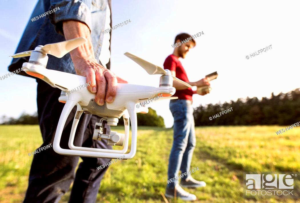 Stock Photo: Senior father and his adult son with drone on a meadow.