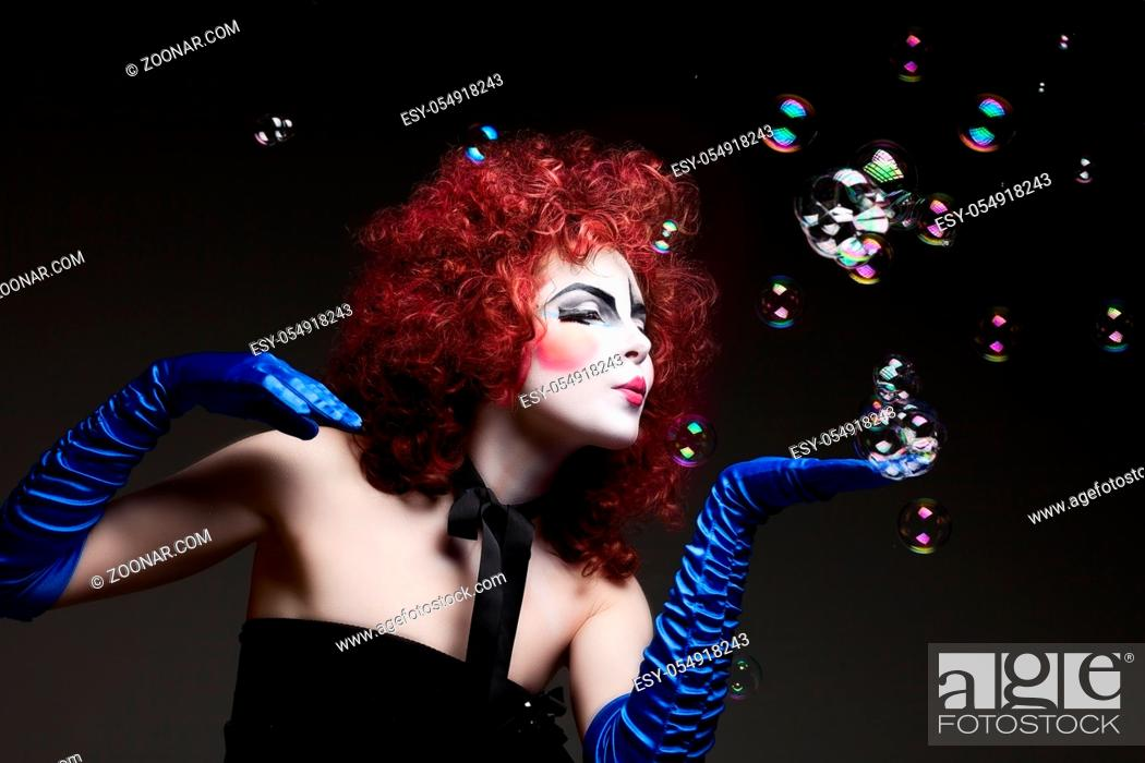 Stock Photo: Woman mime with theatrical makeup and soap bubbles. Studio shot.