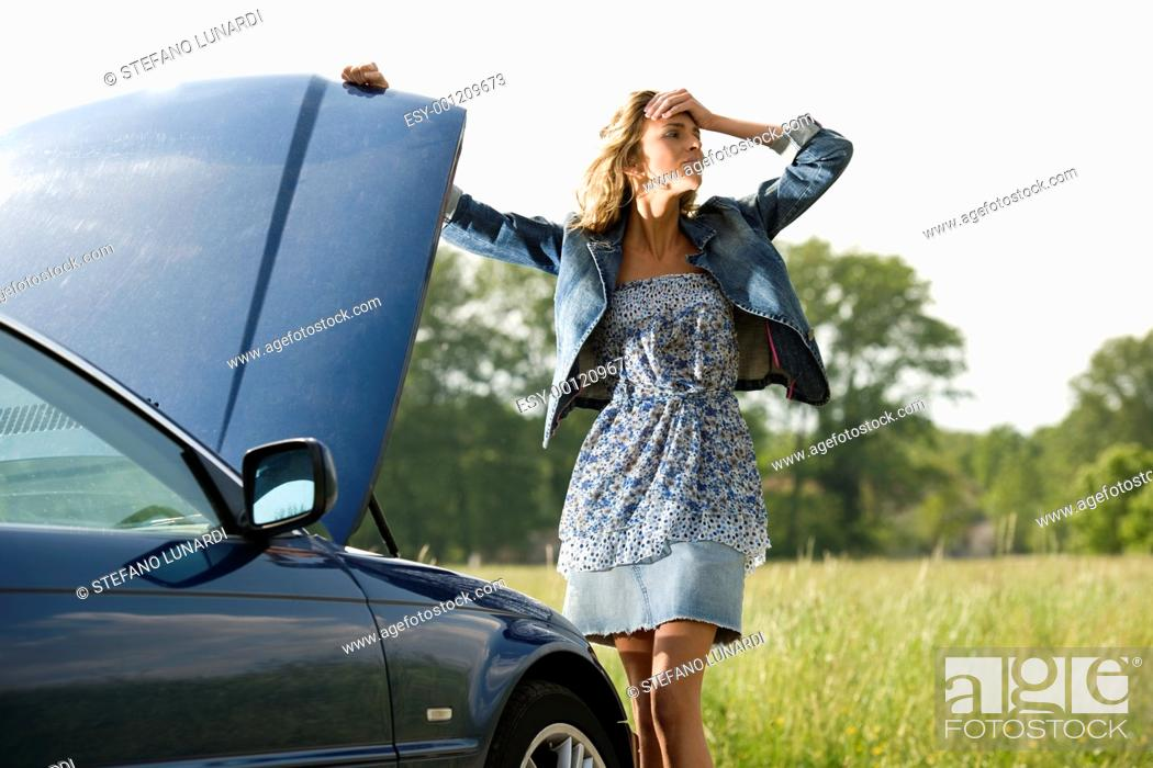 Stock Photo: Worried young woman with her broken car.