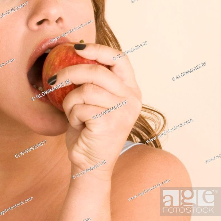 Stock Photo: Young woman eating an apple.