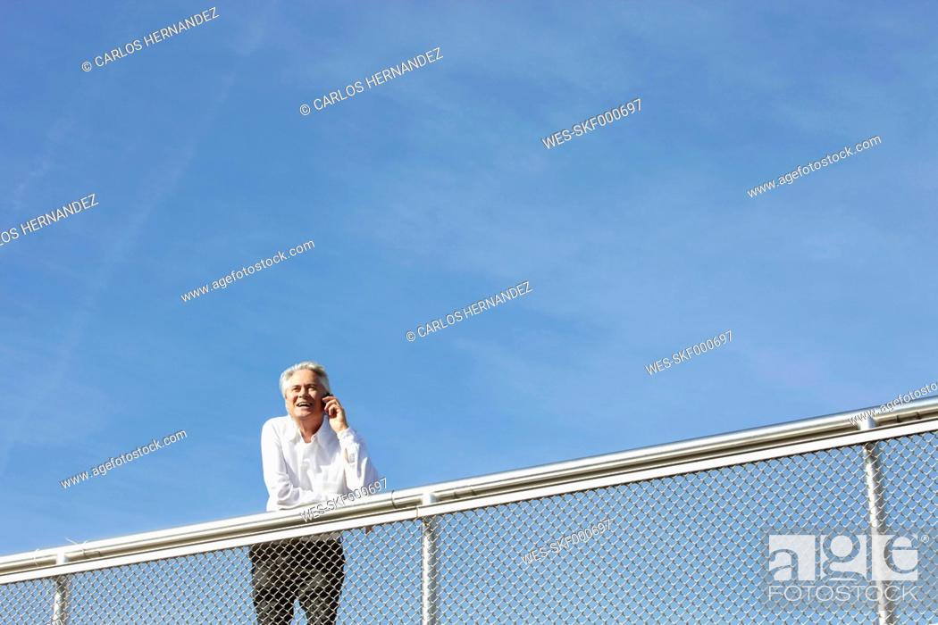 Stock Photo: Germany, Bavaria, Munich, Businessman talking on phone, smiling.