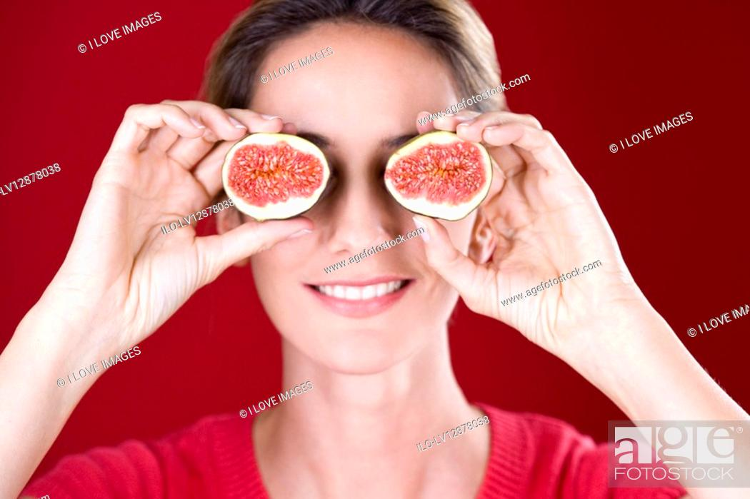 Stock Photo: A mid adult woman holding figs up to her eyes.