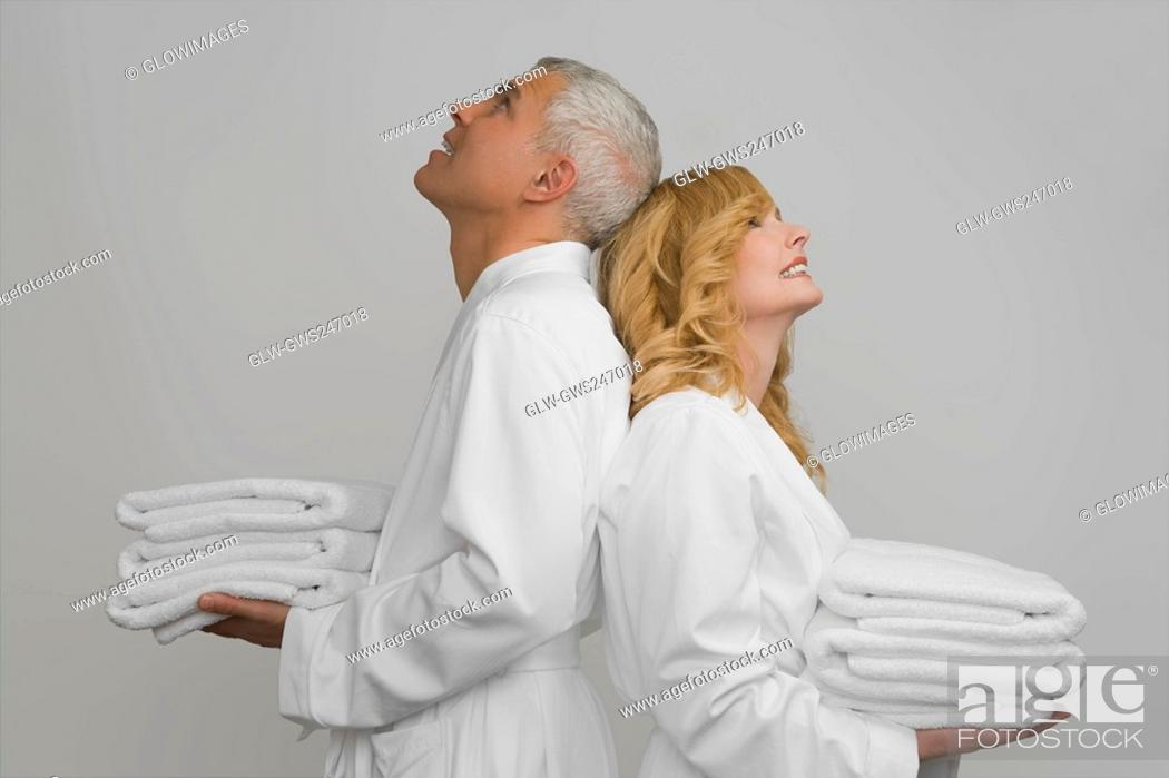 Stock Photo: Side profile of a mature couple standing back to back and holding folded towels.