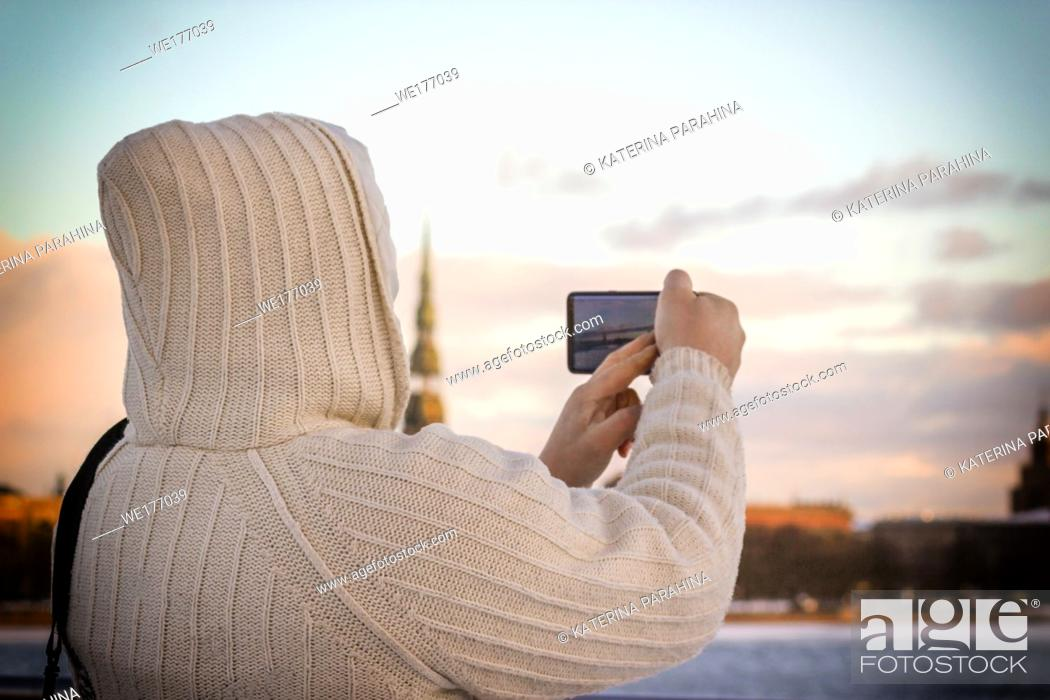 Stock Photo: Man in white knitted jacket taking photo of cityscape with his smartphone in Riga, Latvia.