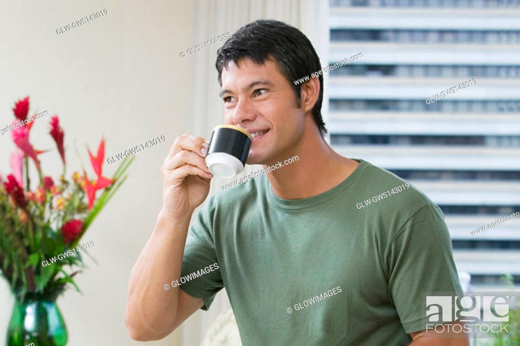 Stock Photo: Mid adult man drinking a cup of tea.