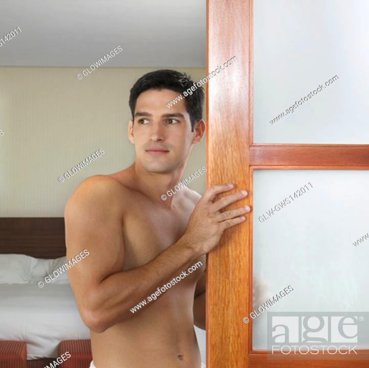 Stock Photo: Side profile of a young man standing near a door.