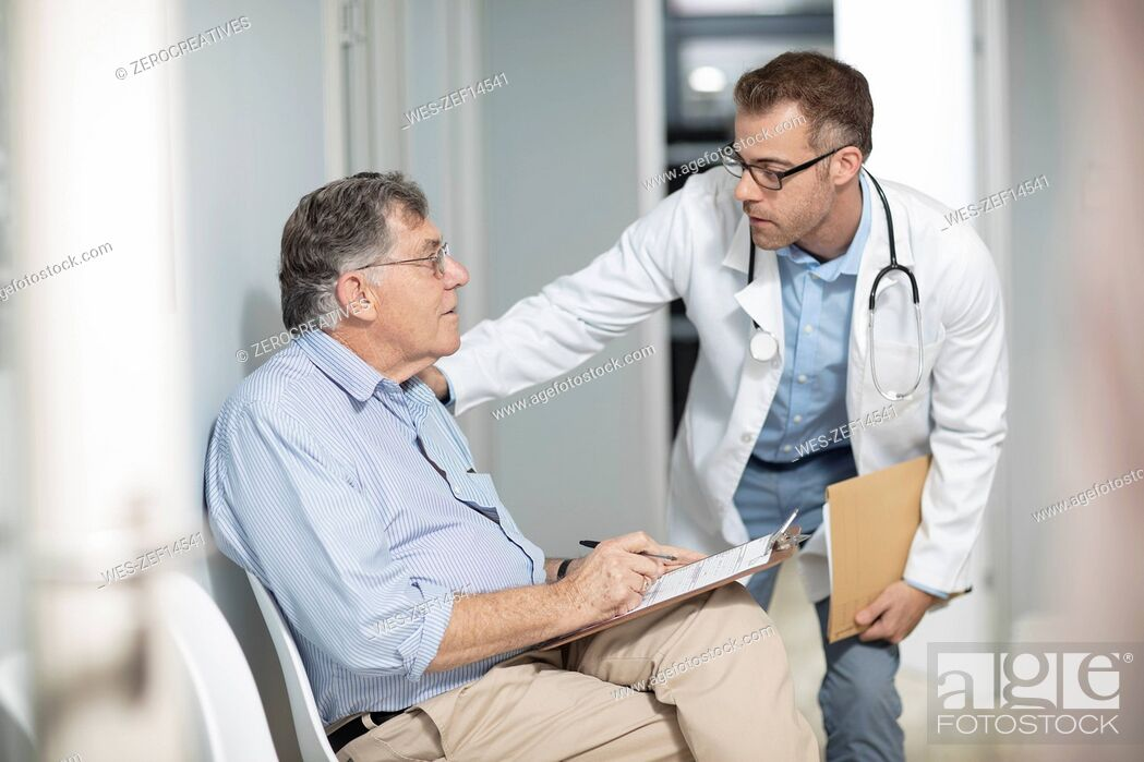 Stock Photo: Doctor talking to patient with file in medical practice.