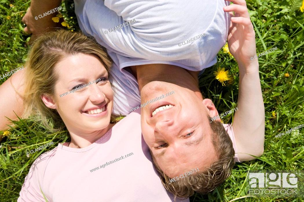 Stock Photo: Germany, Bavaria, Munich, Young couple lying in meadow, smiling, elevated view, portrait.