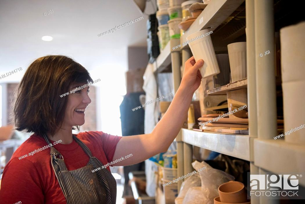 Stock Photo: Smiling Caucasian woman placing cup on shelf in workshop.