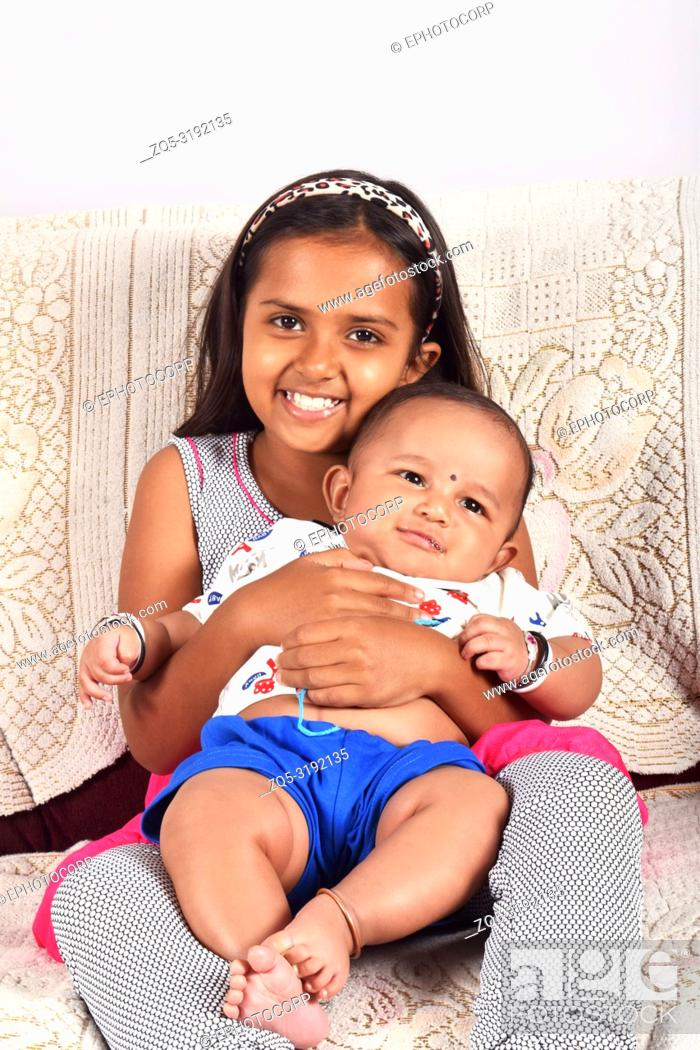 Imagen: Sister hugging happy baby brother sitting on sofa, Pune, Maharashtra.