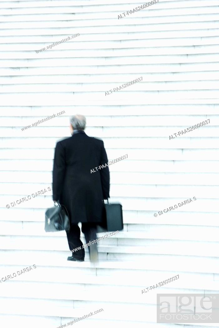 Stock Photo: Businessman carrying two heavy bags slowly going up stairs outdoors.