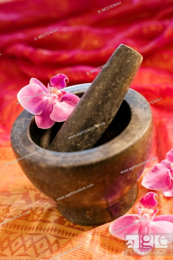 Stock Photo: Mortar with pestle and flowers, close-up.