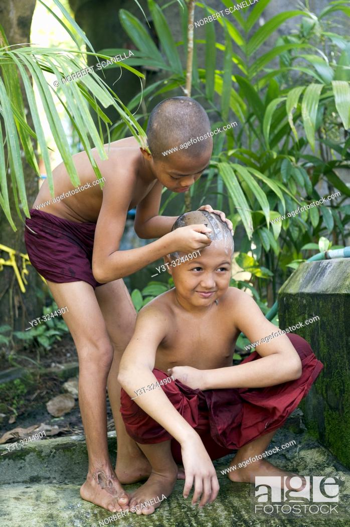 Stock Photo: Myanmar (formerly Burma). Mon State. Mawlamyine (Moulmein). Gaungse Kyun, Shampoo island. Young monks shaving their heads.