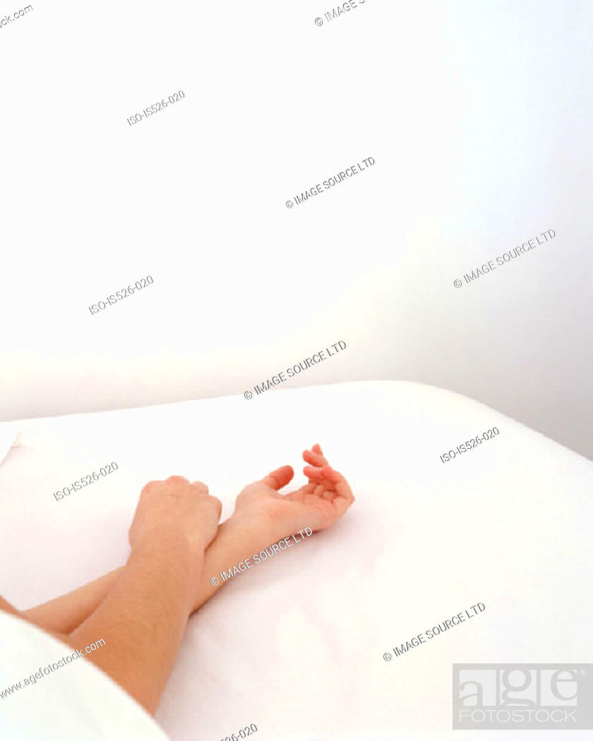Stock Photo: Hand of a female resting on a pillow.