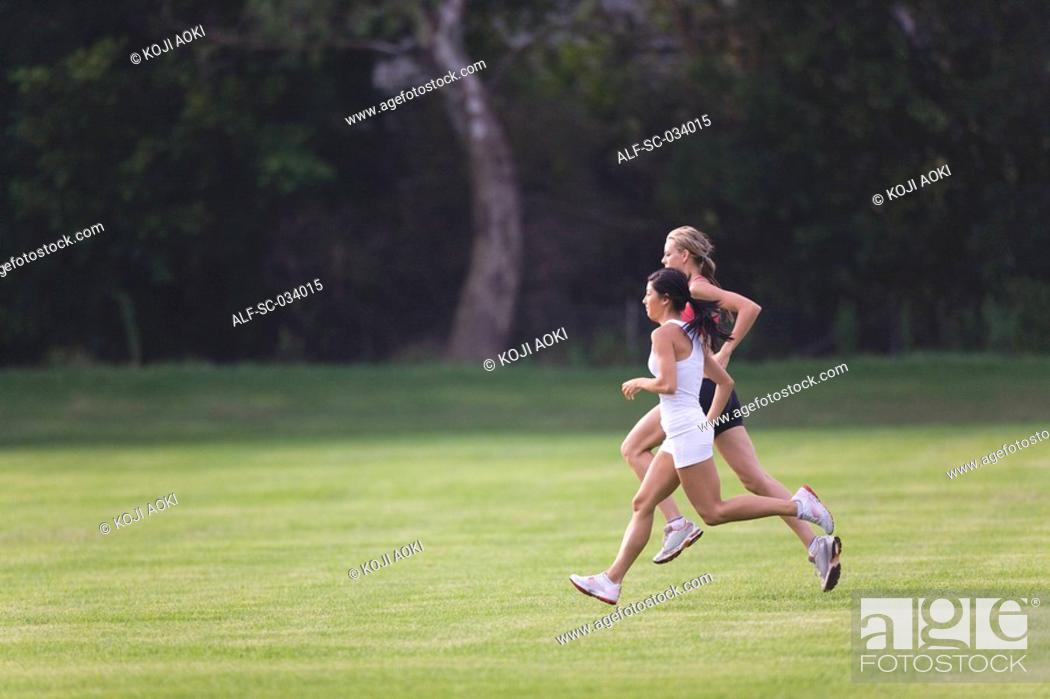 Stock Photo: Two Women Running Together on Grass.