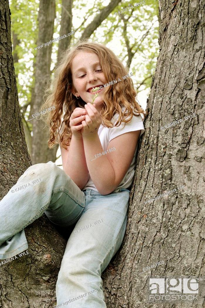Stock Photo: Preteen girl with wavy gold-brown hair and freckles, sitting in tree, in faded jeans and white short-sleeved top, looking at small white wildflower and smiling.