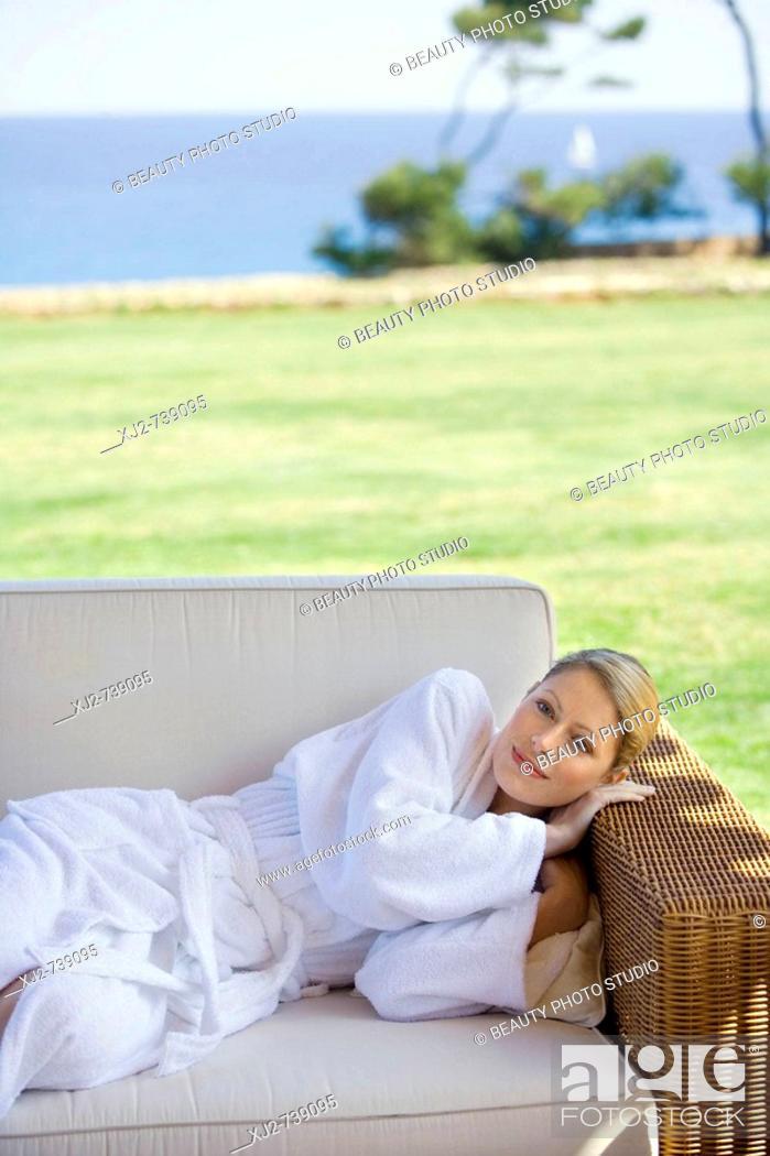 Stock Photo: Woman in bathrobe relaxing outdoors.