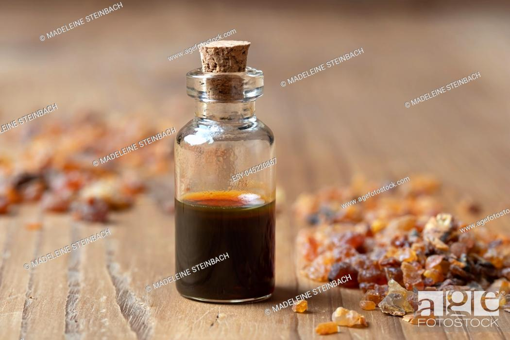 Stock Photo: A bottle of essential oil with myrrh resin crystals.